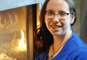 Alex Hughes smiling in a blue shirt in front of a fireplace