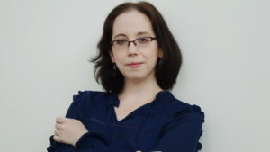 Alex in glasses and a navy colored shirt with her arms crossed, looking serious, competent, and approachable.